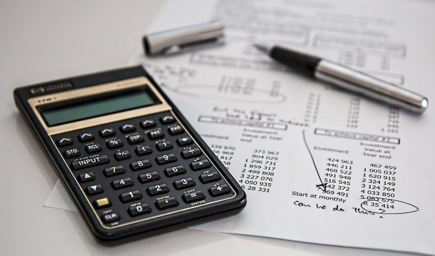 common financial mistakes - calculator with financial worksheet and pen